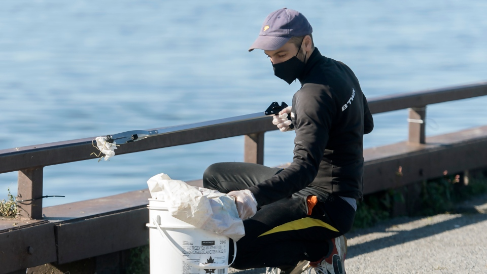 A man picking up trash from the St. Lawrence