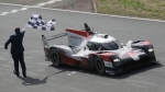 The Toyota TS050 Hybrid No8 of the Toyota Gazoo Racing Team's drivers Sebastien Buemi of Switzerland, Kazuki Nakajima of Japan and Brendon Hartley crosses the finish line to win the 88th 24-hour Le Mans endurance race, in Le Mans, western France, Sunday, Sept. 20, 2020. (AP Photo/David Vincent)