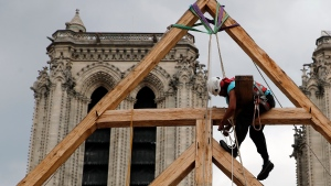 Charles, one of the carpenters puts the skills of their Medieval colleagues on show on the plaza in front of Notre Dame Cathedral in Paris, France, Saturday, Sept. 19, 2020, by reproducing for the public a section of the elaborate carpentry used when the edifice was built. (AP Photo/Francois Mori)