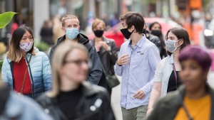 People wear face masks as they walk along a street in Montreal, Saturday, September 19, 2020, as the COVID-19 pandemic continues in Canada and around the world. THE CANADIAN PRESS/Graham Hughes