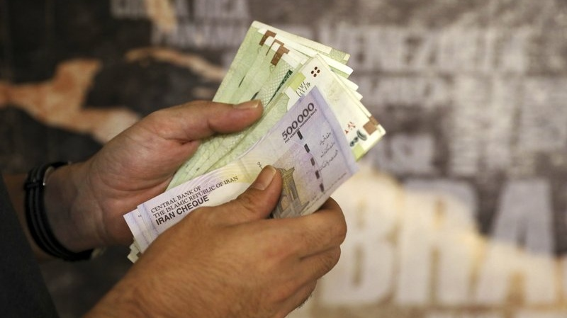 FILE - In this Aug. 21, 2019 file photo, a man counts his banknotes and traveler checks in Tehran, Iran. (AP Photo/Ebrahim Noroozi, File)
