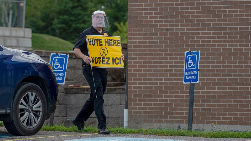 An election worker carries a sign at a voting place for the New Brunswick provincial election in Quispamsis, N.B., Monday, Sept. 14, 2020. Election administrators in British Columbia are ready with hand sanitizer for voters and personal protective equipment for polling-station workers as part of a pandemic plan similar to one used recently in New Brunswick.THE CANADIAN PRESS/Andrew Vaughan