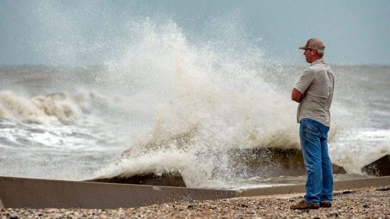 Cole Broom stands on the beach near the intersection of Highway 124 and Highway 87 on the Bolivar Peninsula, Texas, watching the rough surf on Sunday, Sept. 20, 2020. (Fran Ruchalski/The Beaumont Enterprise via AP)