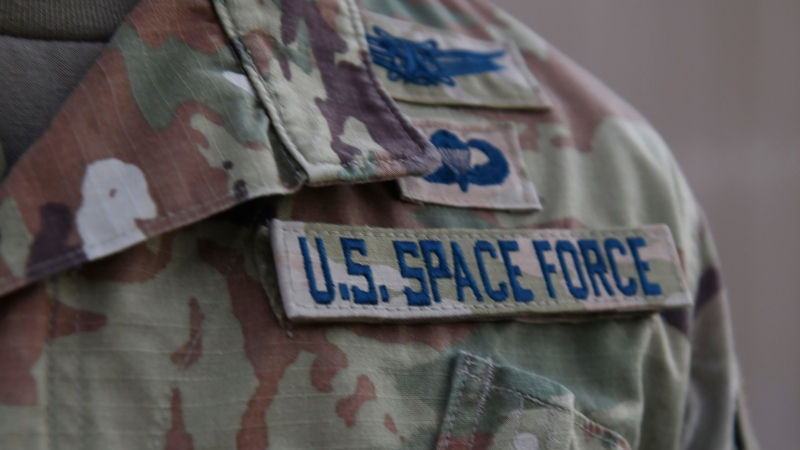 In this photo released by the U.S. Air Force, Capt. Ryan Vickers stands for a photo to display his new service tapes after taking his oath of office to transfer from the U.S. Air Force to the U.S. Space Force at Al-Udeid Air Base, Qatar, Tuesday, Sept. 1, 2020. (Staff Sgt. Kayla White/U.S. Air Force via AP)