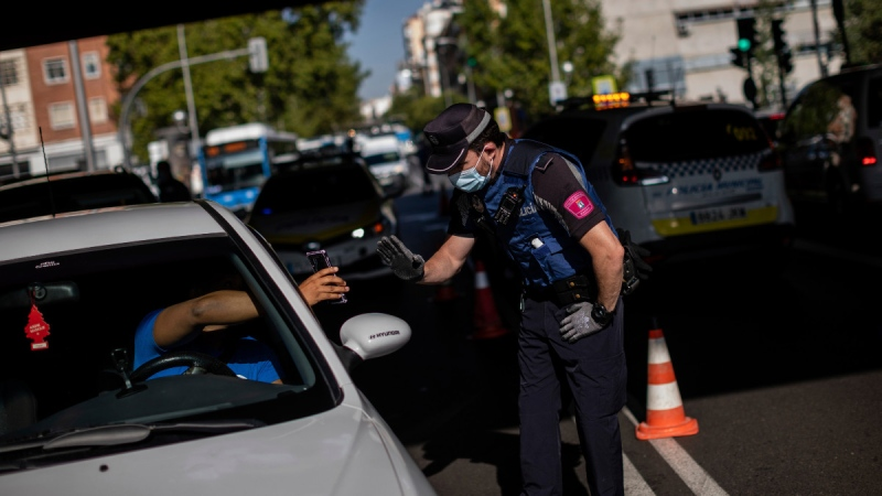 A local police stops a vehicle at a checkpoint in Madrid, Spain, on Sept. 21, 2020. (Bernat Armangue / AP)