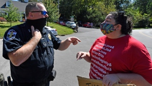 A Louisville Metro police officer talks with a protester in an attempt to get them to get out of the roadway during a protest outside the house of Senate Majority Leader Mitch McConnell, R-Ky., in Louisville, Ky., Saturday, Sept. 19, 2020. (AP Photo/Timothy D. Easley)