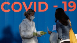 A woman talks to a healthcare worker before getting tested for COVID-19 at a sampling station in Prague, Czech Republic, Monday, Sept. 21, 2020. The country coped well with the first wave of the coronavirus infections in the spring but has been facing a record surge of the new confirmed cases last week. (AP Photo/Petr David Josek)