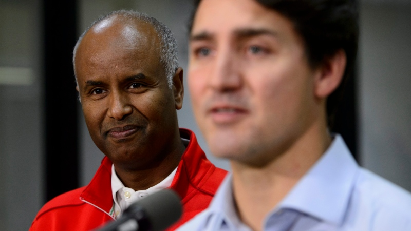 Liberal candidate for York-South Weston Ahmed Hussen, looks on as Liberal leader Justin Trudeau speaks to the media at a Thanksgiving food drive in Toronto on Sunday, Oct. 13, 2019. THE CANADIAN PRESS/Sean Kilpatrick