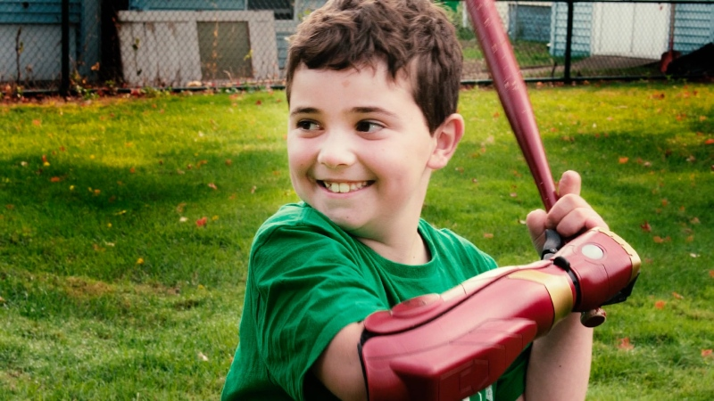 An 8-year-old rare disease survivor from Massachusetts tested his new Iron Man prosthetic arm, which allows him to hold a baseball bat.