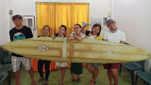 Filipino teacher Giovanne Branzuela (left) and his villagemates pose with the surfboard previously lost by big-wave surfer Doug Falter in Hawaii. (Giovanne Branzuela/Handout/AFP/Getty Images)