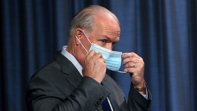 John Horgan puts on his mask following a news conference at the Legislature in Victoria, Wednesday, Sept. 9, 2020. (Chad Hipolito / THE CANADIAN PRESS)