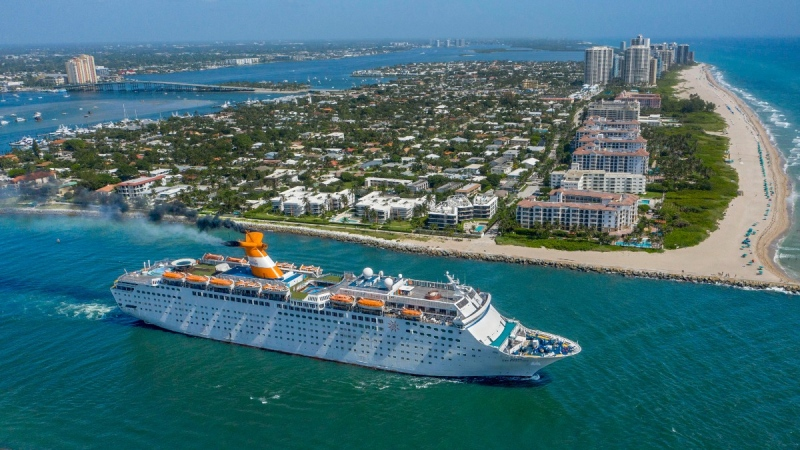 The Grand Celebration cruise ship sails through the Lake Worth Inlet between Palm Beach and Singer Island, Florida, on July 31, 2020. (Greg Lovett / The Palm Beach Post via AP)