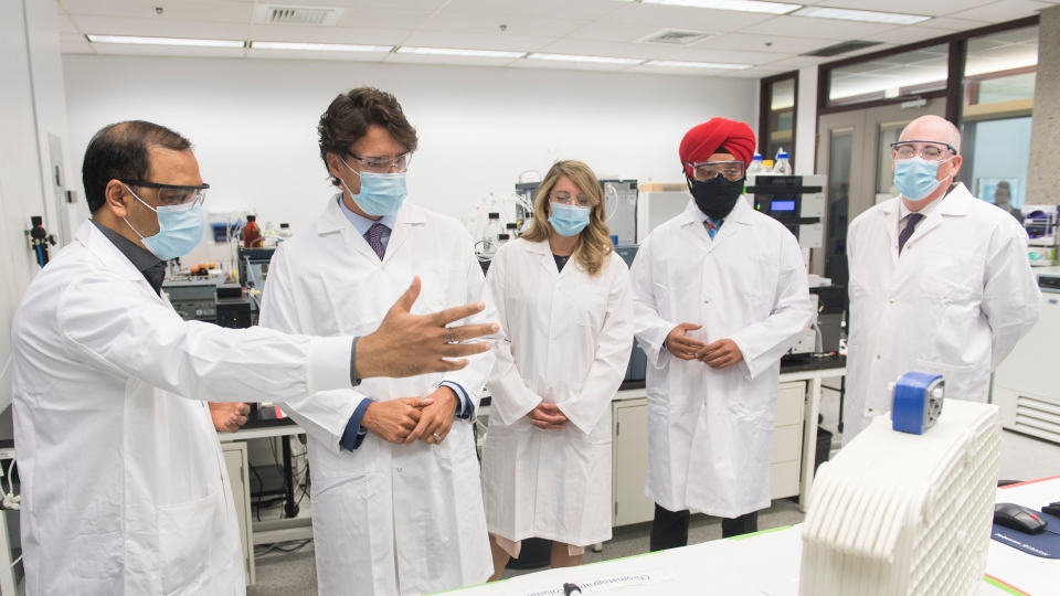 Prime Minister Justin Trudeau, second left, speaks with scientist Krishnaraj Tiwari, left, as Minister of Economic Development Melanie Joly, centre, then-minister of science and industry Navdeep Bains and NRC President Iain Stewart, right, look on during a visit to the National Research Council of Canada (NRC) Royalmount Human Health Therapeutics Research Centre facility in Montreal, Monday, Aug 31, 2020. THE CANADIAN PRESS/Graham Hughes