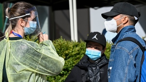 A health-care official takes information as people line up at a COVID assessment centre during the COVID-19 pandemic in Toronto on Friday, September 18, 2020. THE CANADIAN PRESS/Nathan Denette