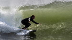 A surfer rides a wave in Cow Bay, N.S., on Monday, Sept. 21, 2020. Hurricane Teddy is expected to impact the Atlantic region starting mid-day Tuesday as a post-tropical storm, bringing rain, wind and high waves. (HE CANADIAN PRESS/Andrew Vaughan)