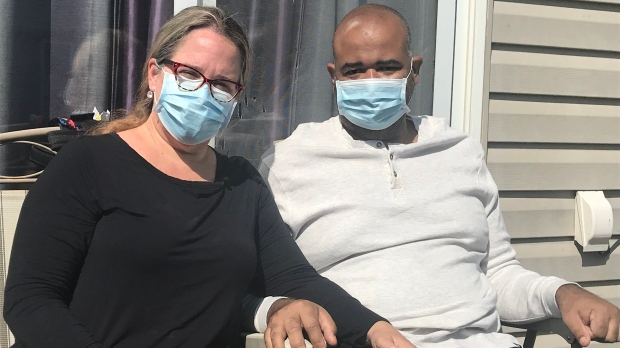Heidi Richardson sits with her husband Torry who is back home after a long battle with COVID-19 in LaSalle, Ont. on Monday, Sept. 21 2020. (Angelo Aversa/CTV Windsor)