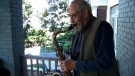 Vic Lawrence is seen playing the saxophone during an outdoor concert.
