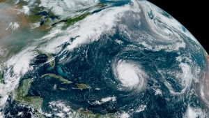 This GOES-16 GeoColor satellite image taken Friday, Sept. 18, 2020, at 12:20 p.m. EDT., and provided by NOAA, shows Hurricane Teddy, center, in the Atlantic, Tropical Depression 22, left, in the Gulf of Mexico, the remnants Paulette, top right, and Tropical Storm Wilfred, lower right. (NOAA via AP)