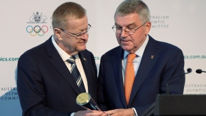 In this May 4, 2019, file photo, International Olympic Committee President Thomas Bach, right, is presented with the Australian Olympic Committee (AOC) President's trophy by AOC president John Coates at the AOC annual general meeting in Sydney, Australia. (AP Photo/Rick Rycroft, File)