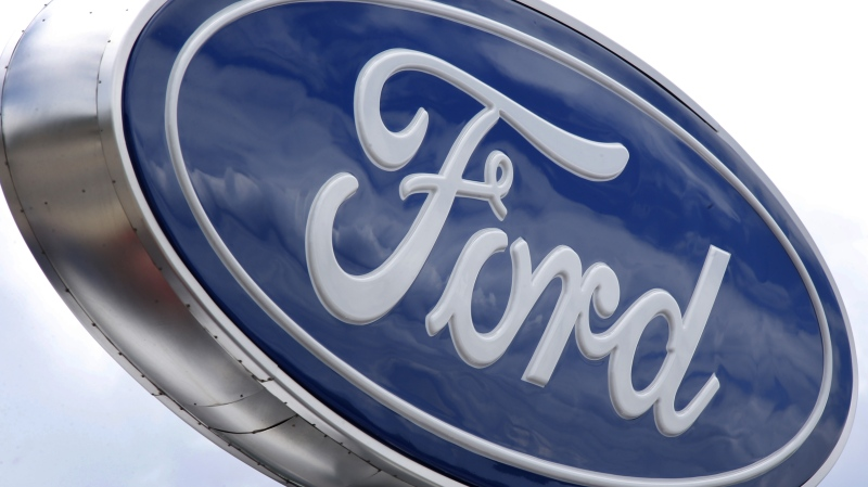 Clouds are reflected in the Ford sign at a dealership in Wexford, Pa, June 5, 2014. (AP Photo/Keith Srakocic)