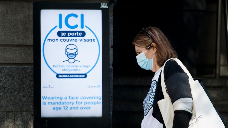 A woman wears a face mask as she walks by a sign advising people on the mandatory wearing of face coverings in Montreal, Monday, September 21, 2020, as the COVID-19 pandemic continues in Canada and around the world. THE CANADIAN PRESS/Graham Hughes