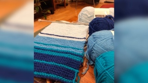 Staff at the University of Alberta's library are making scarves to represent the COVID-19 data in provinces and territories across Canada.