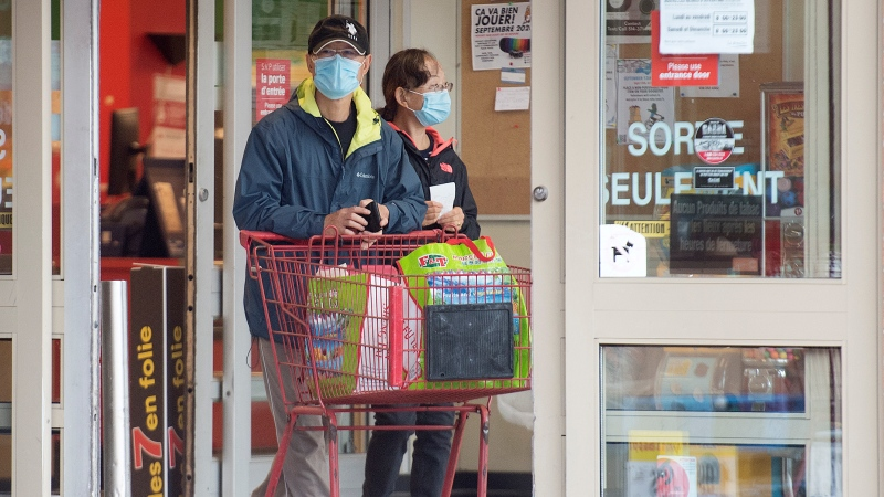 People wear face masks as they leave a grocery store in Montreal, Sunday, Sept. 13, 2020, as the COVID-19 pandemic continues in Canada and around the world. THE CANADIAN PRESS/Graham Hughes