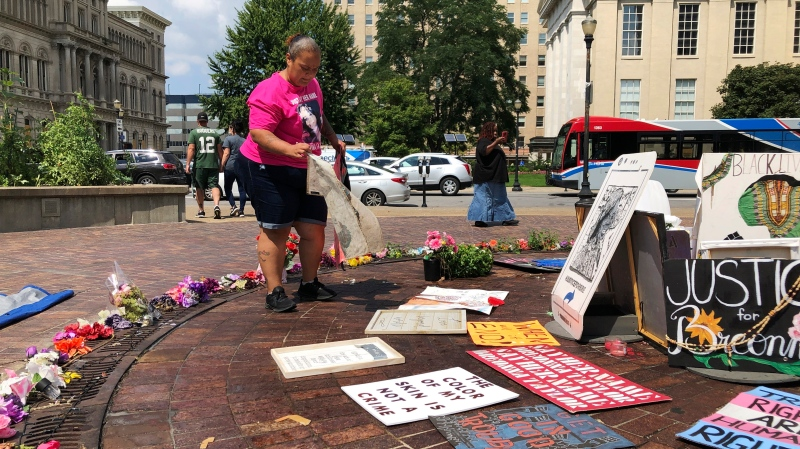 Amber Brown, a Louisville city bus driver, sets up Breonna Taylor artwork at a long-time protest site in Louisville, Ky., Aug. 24, 2020. Brown and others have demonstrated at the downtown public square for months, calling for police officers to be charged in the slaying of Taylor, who was shot in her home March 13. (AP Photo/Dylan Lovan)