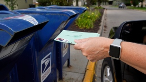 "In this Tuesday, Aug. 18, 2020, file photo, a person drops applications for mail-in-ballots into a mail box in Omaha, Neb. A U.S. judge on Thursday, Sept. 17, 2020, blocked controversial Postal Service changes that have slowed mail nationwide. The judge called them ""a politically motivated attack on the efficiency of the Postal Service"" before the November election. (AP Photo/Nati Harnik, File)"