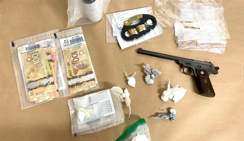 Officers seized a loaded .22 caliber pistol, brass knuckles, more than 29 grams of suspected cocaine, 64 squares of Lysergic Acid Diethylamide (LSD) and more than $1,900 in Canadian currency. (Supplied)
