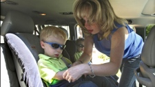 Sharon Waldrop helps her son Jack in his car seat in Royal Oak, Mich., Tuesday, July 7, 2009.  (AP Photo/Carlos Osorio)
