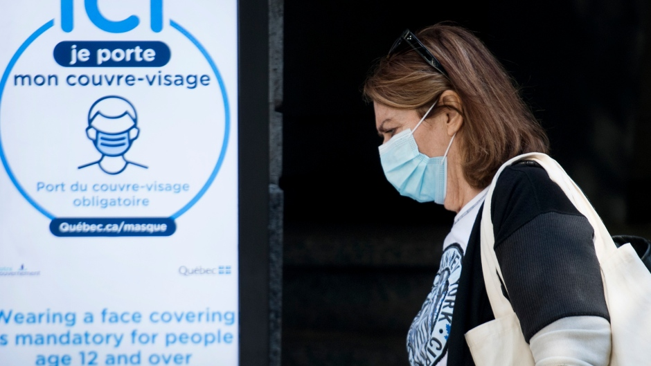 In this file photo, a woman wears a face mask as she walks by a sign advising people on the mandatory wearing of face coverings in Montreal, Monday, September 21, 2020, as the COVID-19 pandemic continues in Canada and around the world. THE CANADIAN PRESS/Graham Hughes