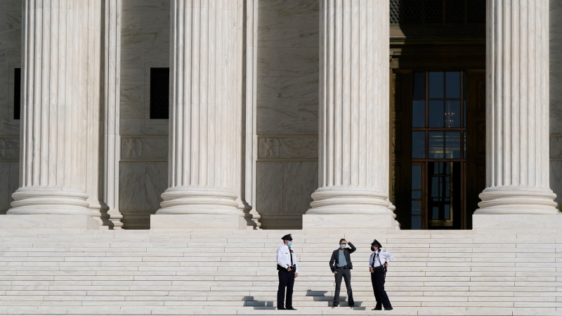 Officials stand on the Supreme Court steps on Capitol Hill in Washington, Tuesday, Sept. 22, 2020, as preparations take place for a private ceremony and public viewing in remembrance of Justice Ruth Bader Ginsburg. (AP Photo/Patrick Semansky)