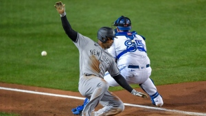 New York Yankees' Aaron Hicks slides past Toronto Blue Jays catcher Alejandro Kirk to score on a single by Gleyber Torres during the fifth inning of a baseball game in Buffalo, N.Y., Tuesday, Sept. 22, 2020. (AP Photo/Adrian Kraus)