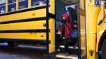 A student walks off the bus at the Bancroft Elementary School in Montreal, on Monday, August 31, 2020. THE CANADIAN PRESS/Paul Chiasson