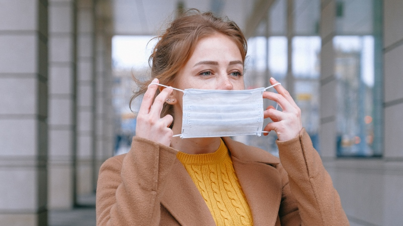 A woman puts on a face mask in this stock photo. (Anna Shvets / Pexels)