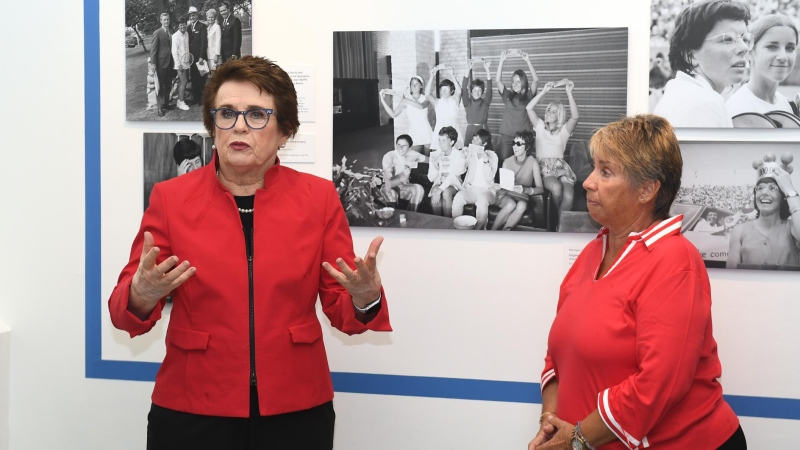Billie Jean King (left) and Rosie Casals stand in front of a photo of the members of the Original 9 holding one dollar notes. (Emilee Chinn/Getty Images North America/Getty Images/CNN)