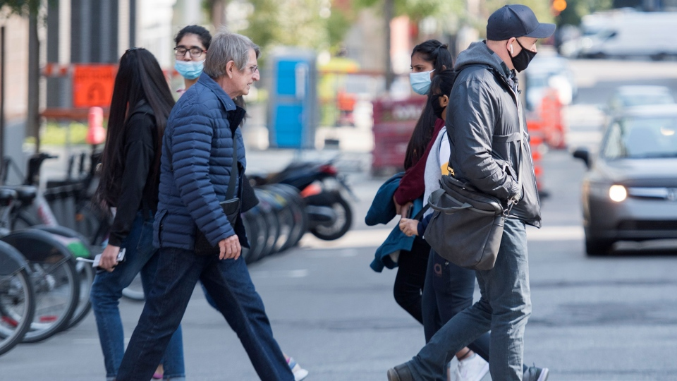 Some wear face masks as they walk along a street in Montreal, Monday, September 21, 2020, as the COVID-19 pandemic continues in Canada and around the world. THE CANADIAN PRESS/Graham Hughes