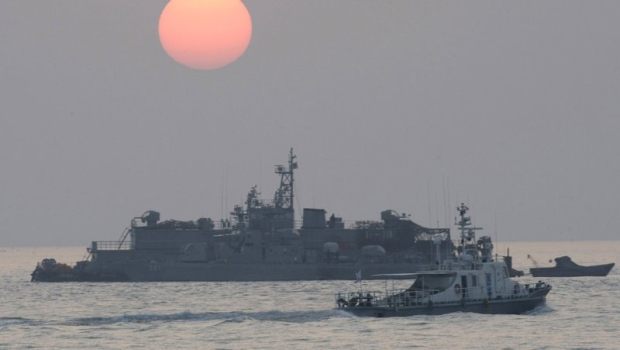 FILE - In this Dec. 22, 2010, file photo, a government ship sails past the South Korean Navy's floating base as the sun rises near Yeonpyeong island, South Korea. (AP Photo/Ahn Young-joon, File)
