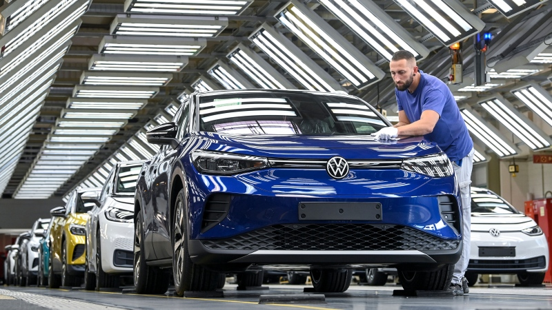 In this photo taken on Sept. 18, 2020, an employee puts finishing touches to a VW ID.4 Volkswagen at the Volkswagen plant in Zwickau, Germany. (Hendrik Schmidt/dpa via AP)