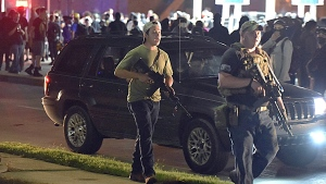 In this Aug. 25, 2020, file photo, Kyle Rittenhouse, left, with backwards cap, walks along Sheridan Road in Kenosha, Wis., with another armed civilian. (Adam Rogan/The Journal Times via AP, File)