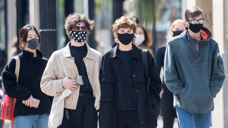People wear face masks as they wait to cross a street in Montreal, Monday, September 21, 2020, as the COVID-19 pandemic continues in Canada and around the world. THE CANADIAN PRESS/Graham Hughes