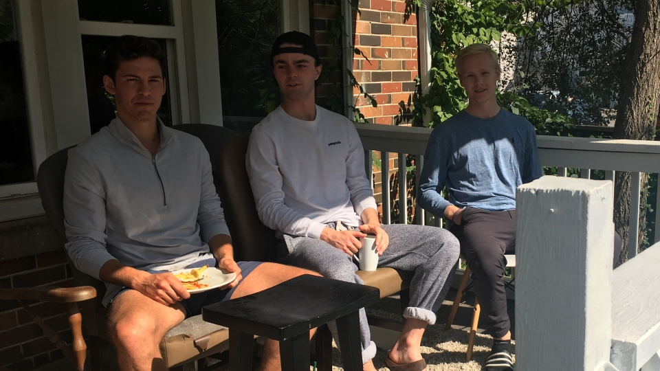 Western University student Calvin Gallina, left, and his roommates sit on their front porch on Broughdale Avenue in London, Ont. on Wednesday, Sept. 23, 2020. (Brent Lale / CTV News)