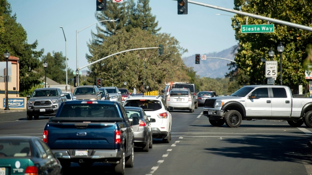 Vehicles backs up on Highway 12 as traffic signals remain dark during a power outage on Wednesday, Oct. 9, 2019, in Boyes Hot Springs, Calif. (AP Photo/Noah Berger)