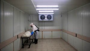 "A worker from ""Hevra Kadisha,"" Israel's official Jewish burial society, prepares a body before a funeral procession at a special morgue for COVID-19 victims in the central Israeli city of Holon, near Tel Aviv, Wednesday, Sept. 23, 2020. With Israel facing one of the world's worst outbreaks, burial workers have been forced to wear protective gear and take other safety measures as they cope with a growing number of coronavirus-related deaths. (AP Photo/Oded Balilty)"