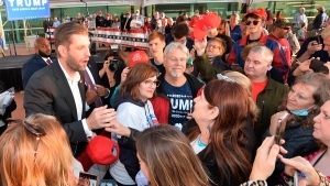 Eric Trump, left, greets well-wishers following a rally, Monday, Sept. 21, 2020, in support of his father, U.S. President Donald Trump, under a tent outside the Bayfront Convention Center in Erie, Pennsylvania. (Christopher Millette/Erie Times-News via AP)
