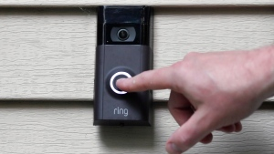 In this July 16, 2019, file photo, a person pushes the doorbell on their Ring doorbell camera. (AP Photo/Jessica Hill, File)