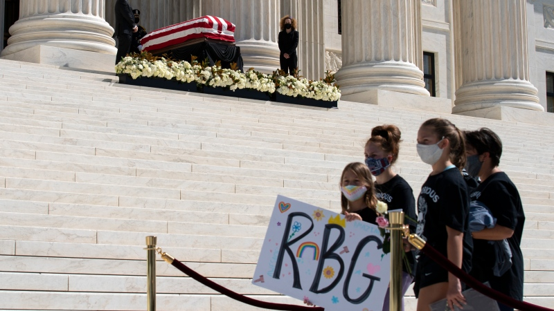 Mourners pay their respect to the flag-draped casket of Justice Ruth Bader Ginsburg at the steps of the U.S. Supreme Court in Washington, Wednesday, Sept. 23, 2020. Ginsburg, 87, died of cancer on Sept. 18. (AP Photo/Jose Luis Magana)