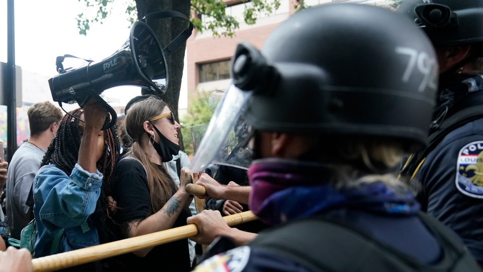 Protesters chant near police, Wednesday, Sept. 23, 2020, in Louisville, Ky. (AP Photo/Darron Cummings)