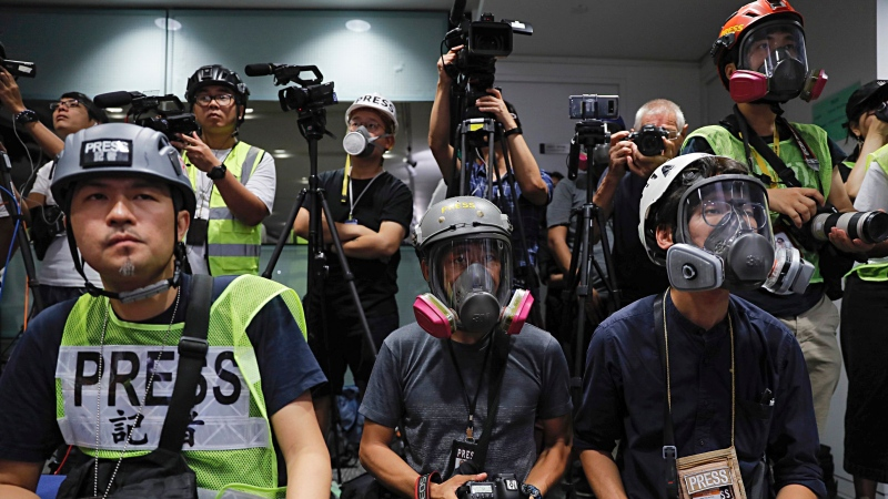 In this Monday, Sept. 9, 2019, file photo, in a sign of protest against the police using force against the media, press photographers wear protective gear during a police media conference in Hong Kong. (AP Photo/Kin Cheung)